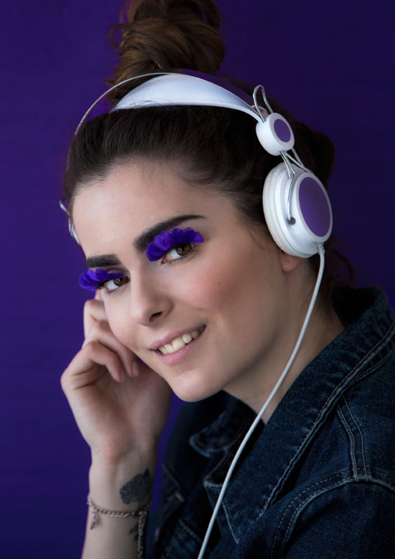 Pretty model listening to music with blue, feather eyelashes