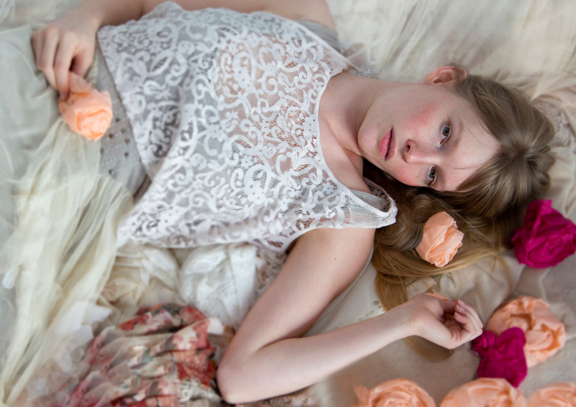 Young model, laying on bed with flowers