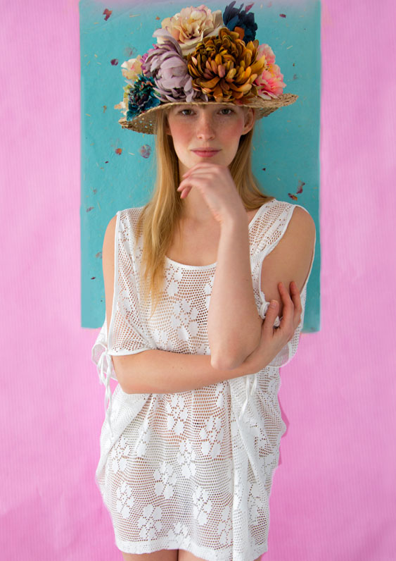 Model with summer hat with flowers on pink background