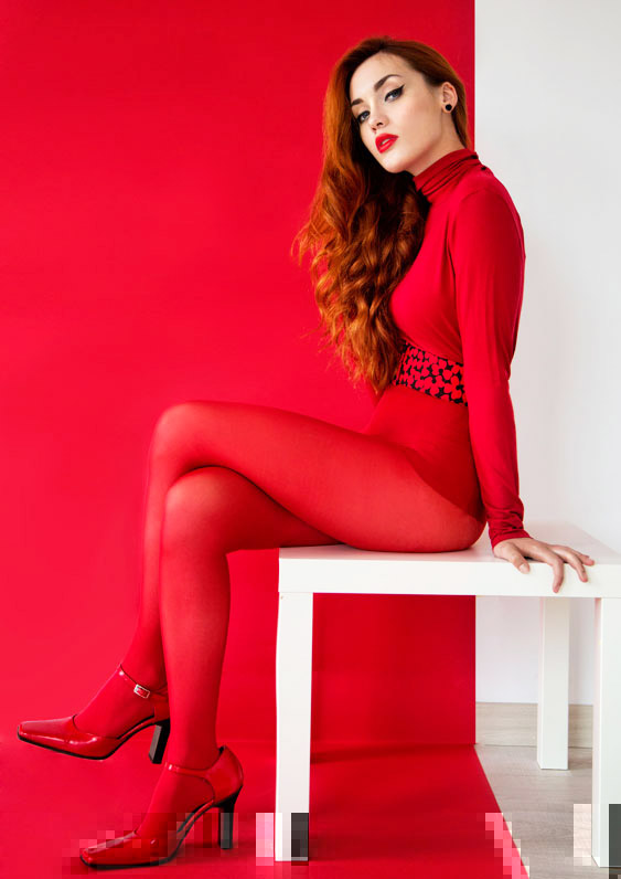 Sexy model in red clothes sitting on the table, by Magdalena Czajka